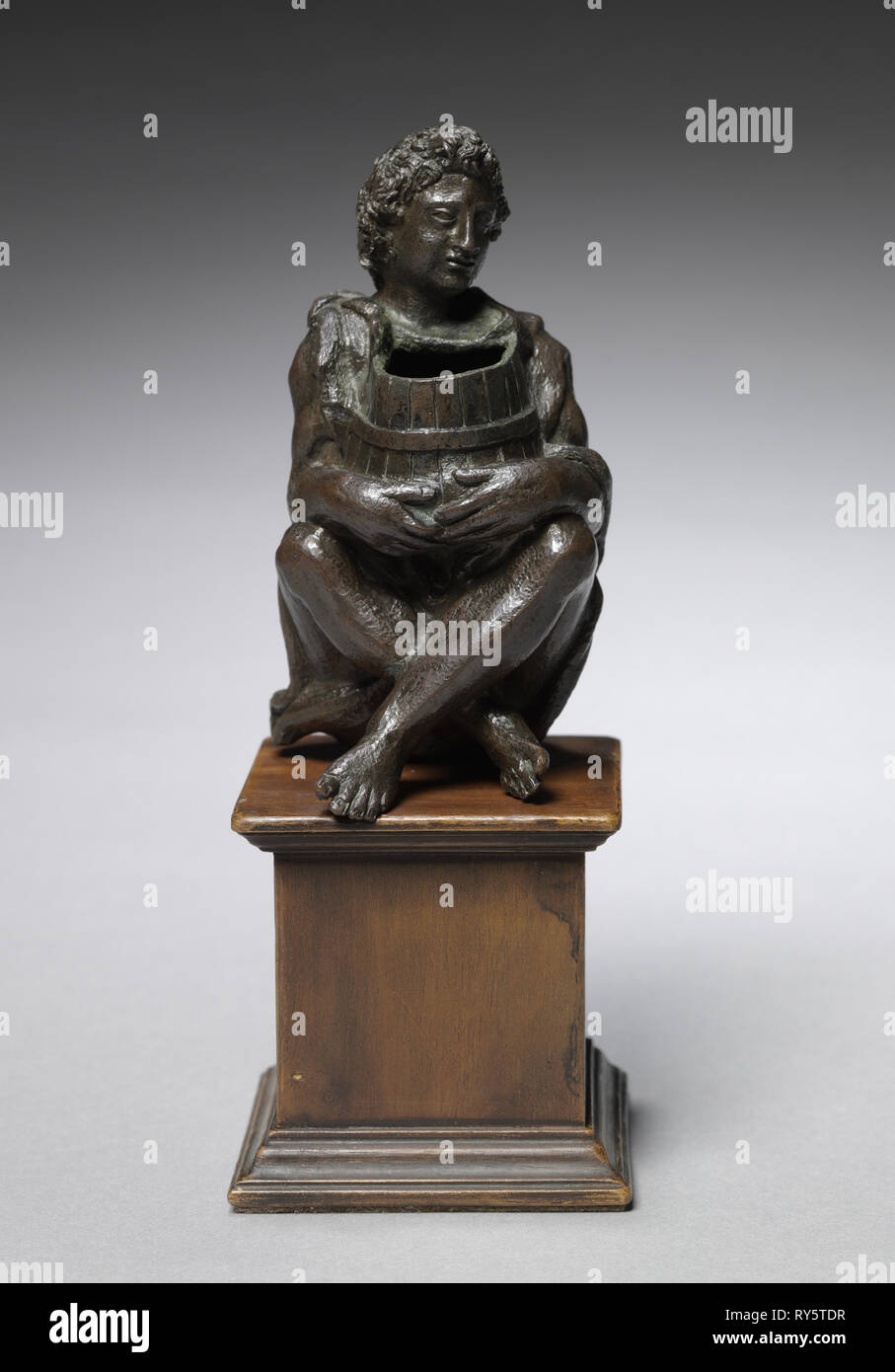 Seated Boy Clothed with Goat Skins Holding an Open Barrel, c. 1525. Italy, Padua, 16th century. Bronze; overall: 11.2 x 6 x 6.5 cm (4 7/16 x 2 3/8 x 2 9/16 in Stock Photo