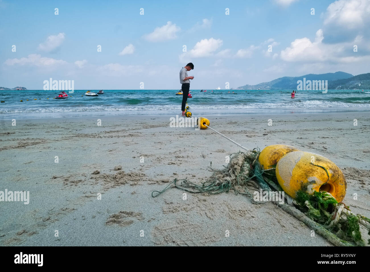 On an overcast morning at Patong Beach, Phuket, Thailand, a lone Thai man forlornly looks at his mobile phone - Stock Image