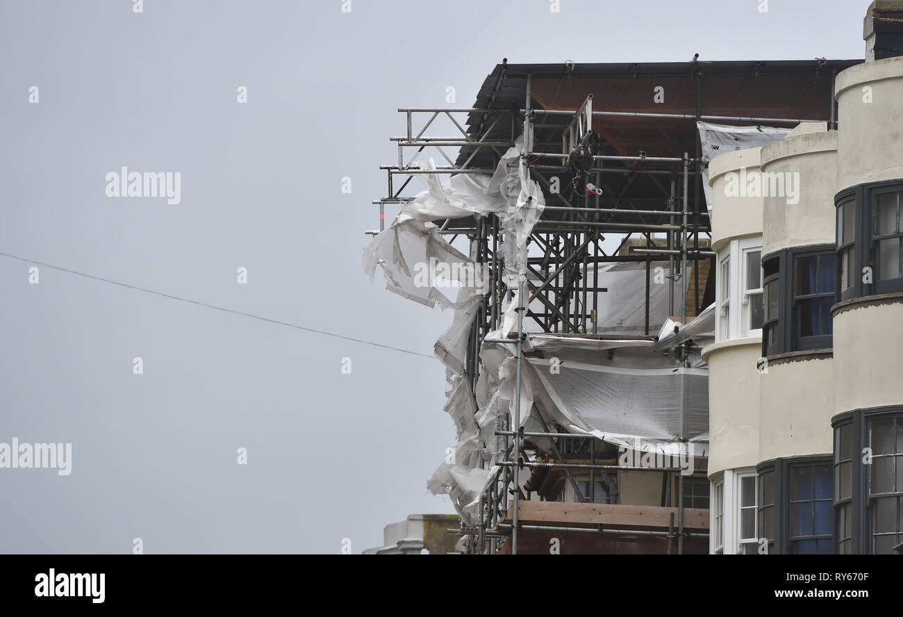 Brighton, UK. 12th Mar, 2019. Protective covers are blown from scaffolding in Brighton as Storm Gareth arrives in Britain and Ireland with wind speeds forecast to reach up to 70 mph in some areas Credit: Simon Dack/Alamy Live News - Stock Image