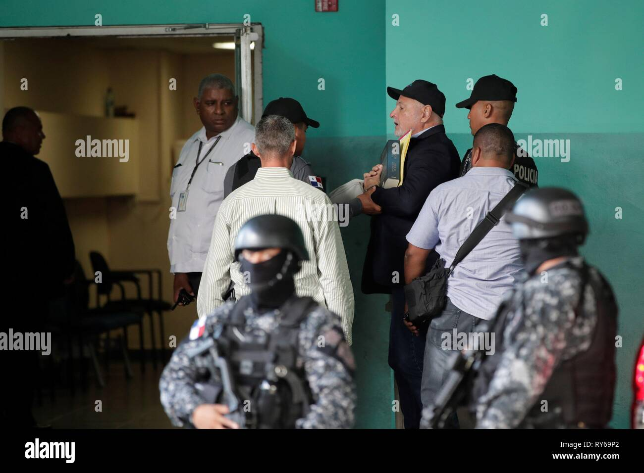 Former President of Panama, Ricardo Martinelli (C), is escorted by the Police upon his arrival at the accusatory penal system court for the trial against him charged with telephone wiretaps during his 2009-2014 term in Panama City, Panama, 12 March 2019. The trial of current candidate for mayor and deputy Ricardo Martinelli begins today and he could receive a sentence of up to 21 years. EFE/ Welcome Velasco - Stock Image
