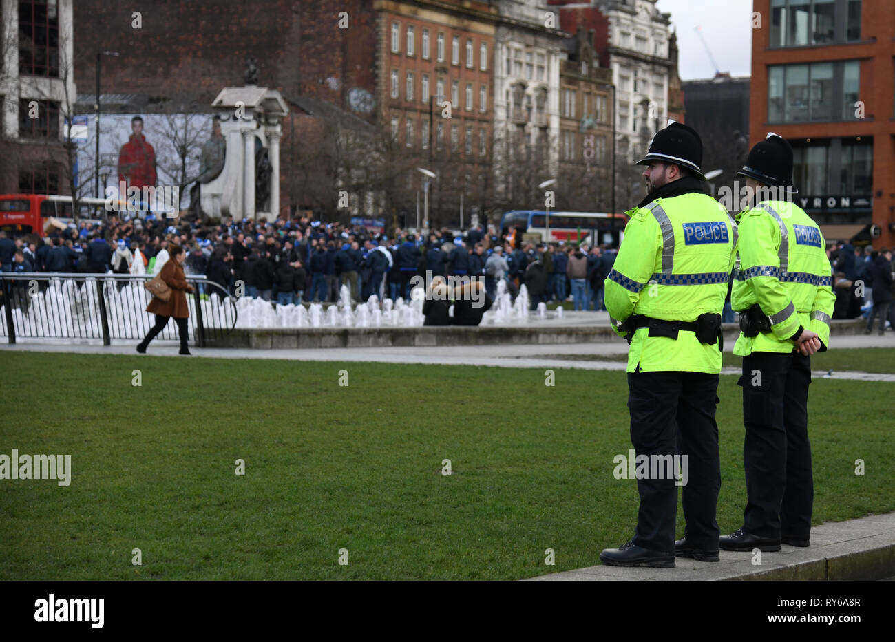 Manchester, UK. 12th Mar, 2019. Soccer: Champions League, Manchester City - FC Schalke 04, knockout round, round of sixteen, return match at Etihad Stadium. Policemen are watching fans of Schalke at Picadilly Gardens Square. Credit: Ina Fassbender/dpa/Alamy Live News - Stock Image