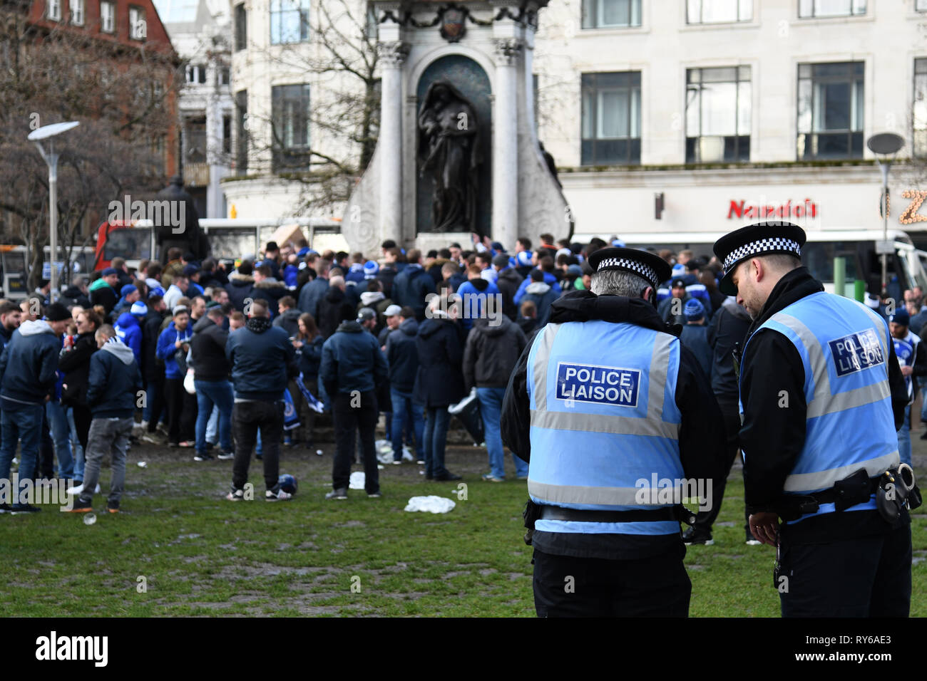 12 March 2019, Great Britain, Manchester: Soccer: Champions League, Manchester City - FC Schalke 04, knockout round, round of sixteen, return match at Etihad Stadium. Policemen are watching fans of Schalke at Picadilly Gardens Square. Photo: Ina Fassbender/dpa - Stock Image