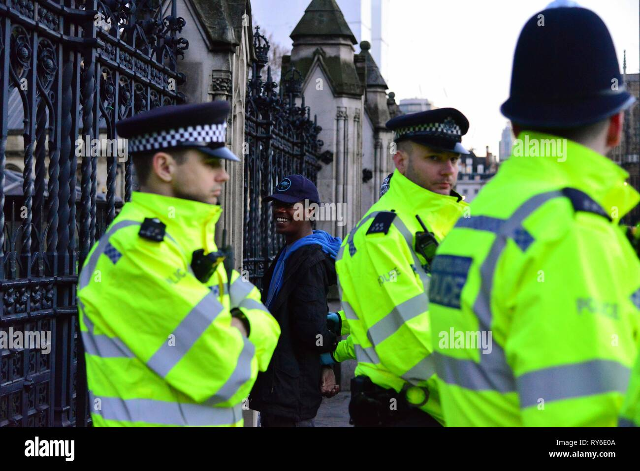 London, UK. 12th Mar, 2019. A man is handcuffed outside the Houses of Parliament after disturbing flowers left at a memorial for murdered  PC Keith Palmer. Credit: Claire Doherty/Alamy Live News - Stock Image