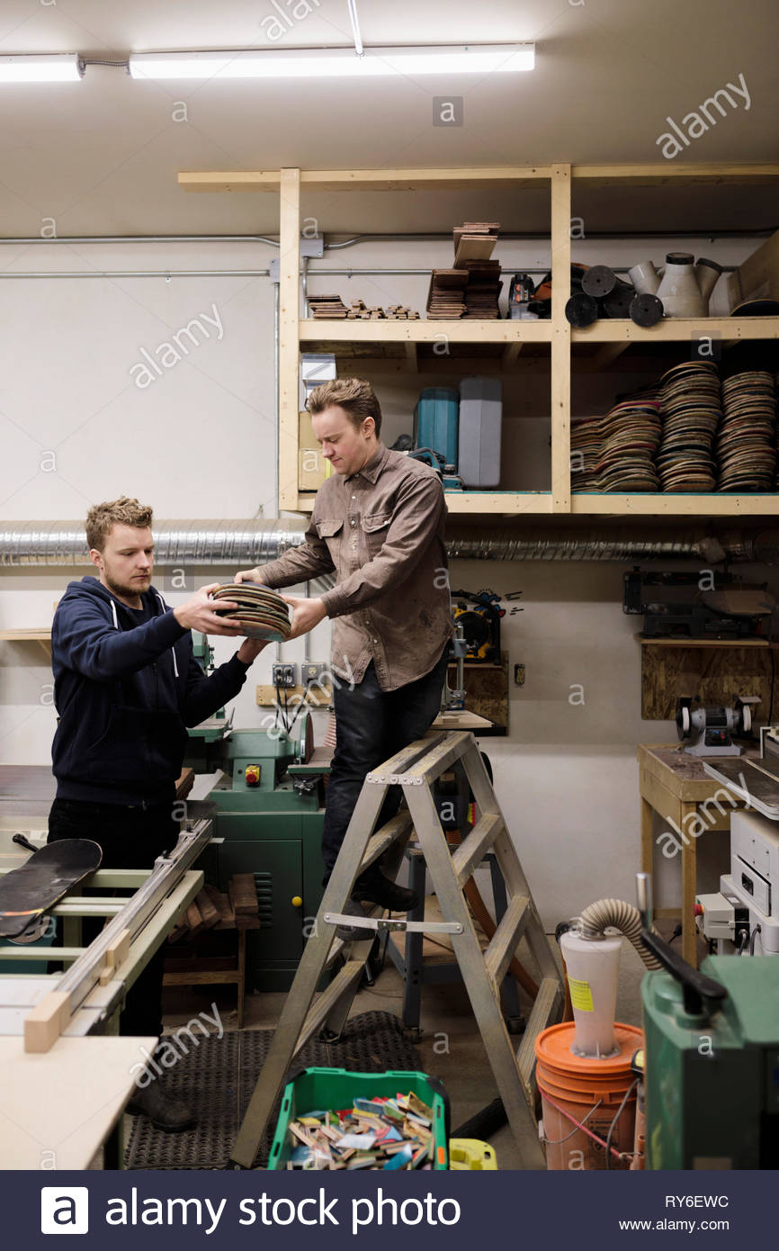 Male artists using recycled skateboards in workshop - Stock Image