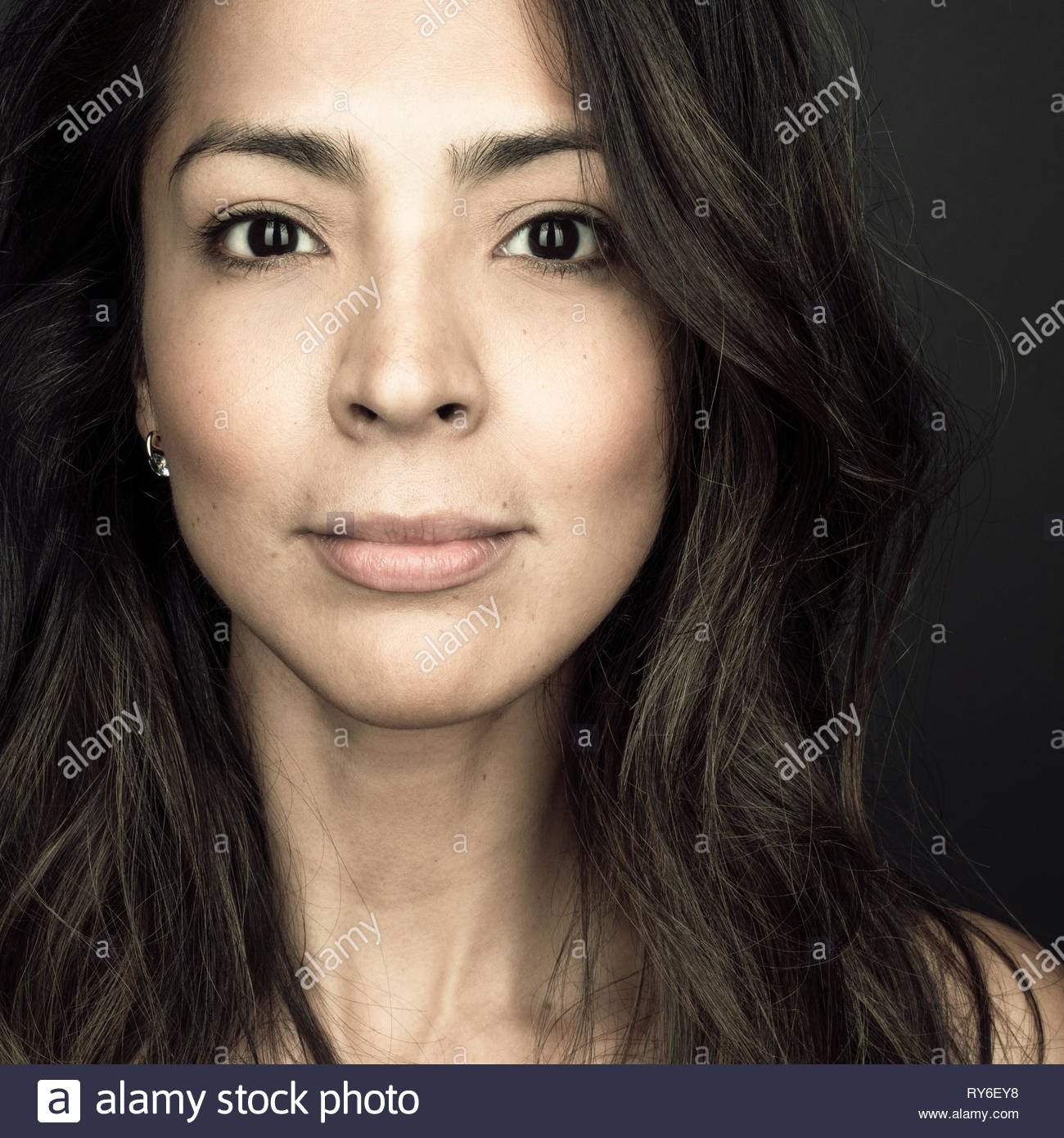 Close up portrait confident beautiful brunette Latina woman with brown eyes - Stock Image