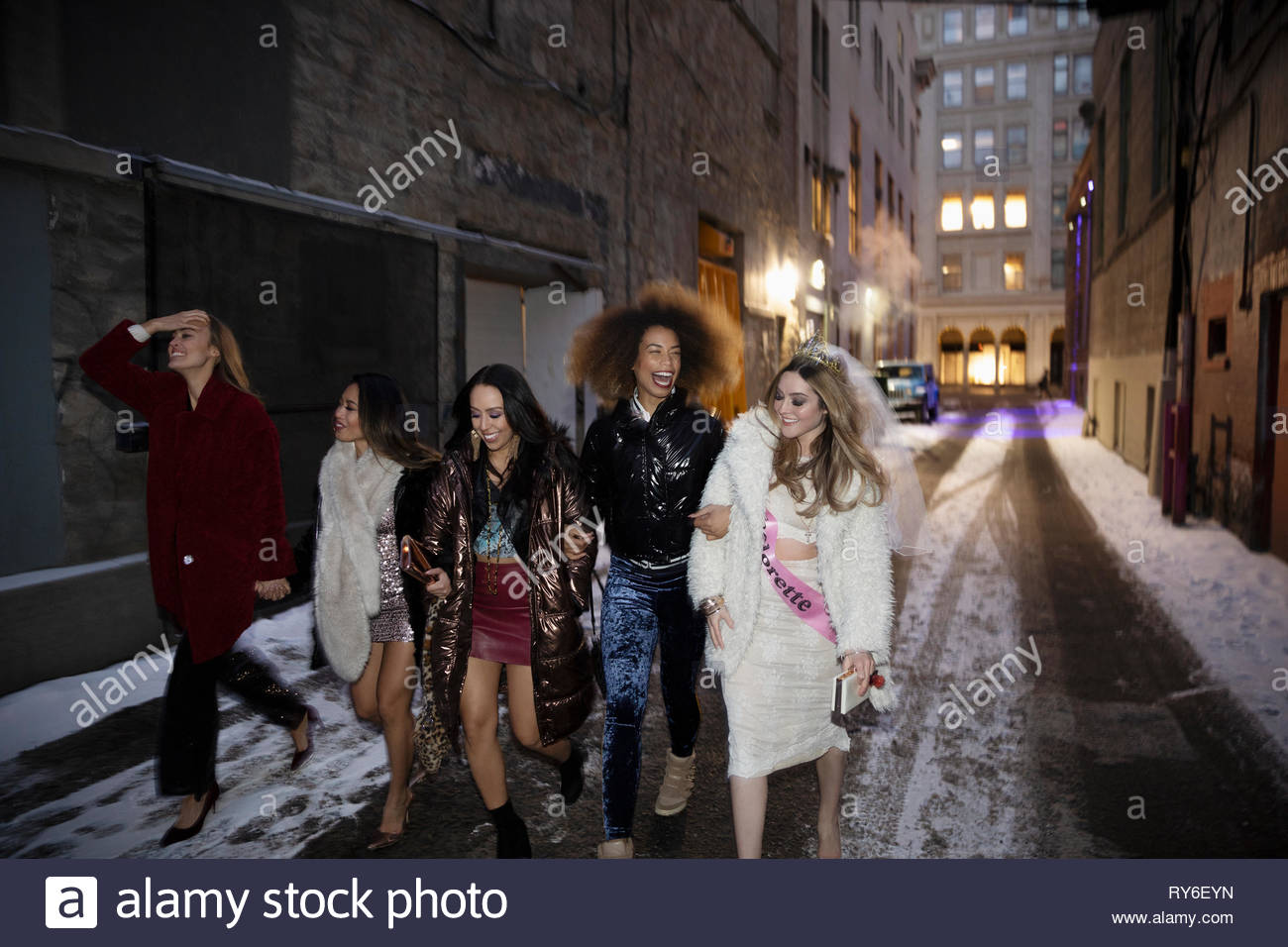 Bachelorette and friends walking along snowy urban alley at night - Stock Image