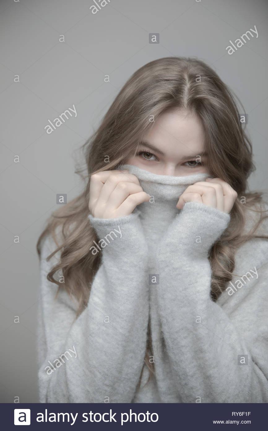 Portrait playful beautiful teenage girl hiding in sweater - Stock Image
