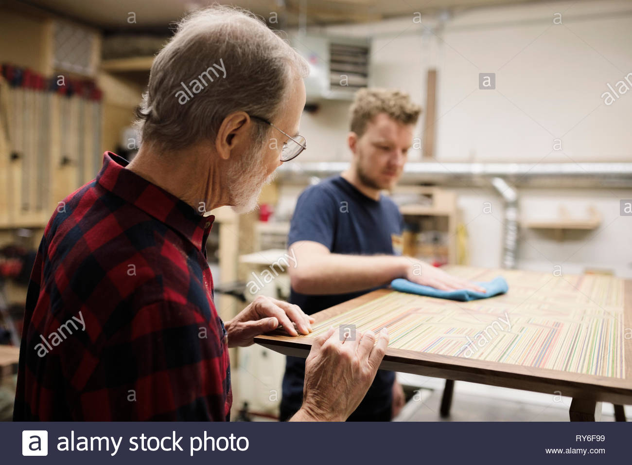 Father and son carpenters finishing table in workshop - Stock Image