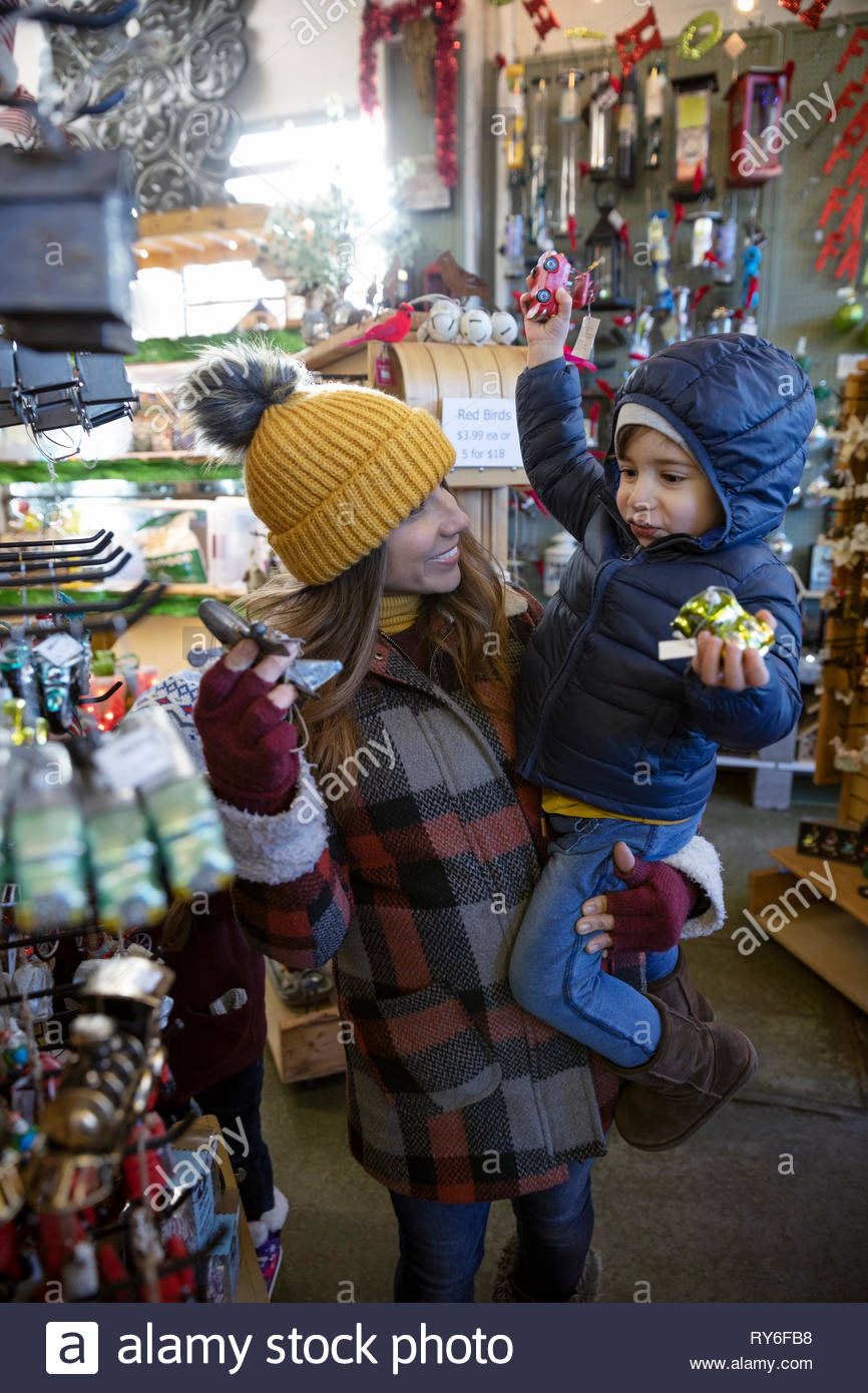 Mother and son picking out ornaments at christmas market - Stock Image