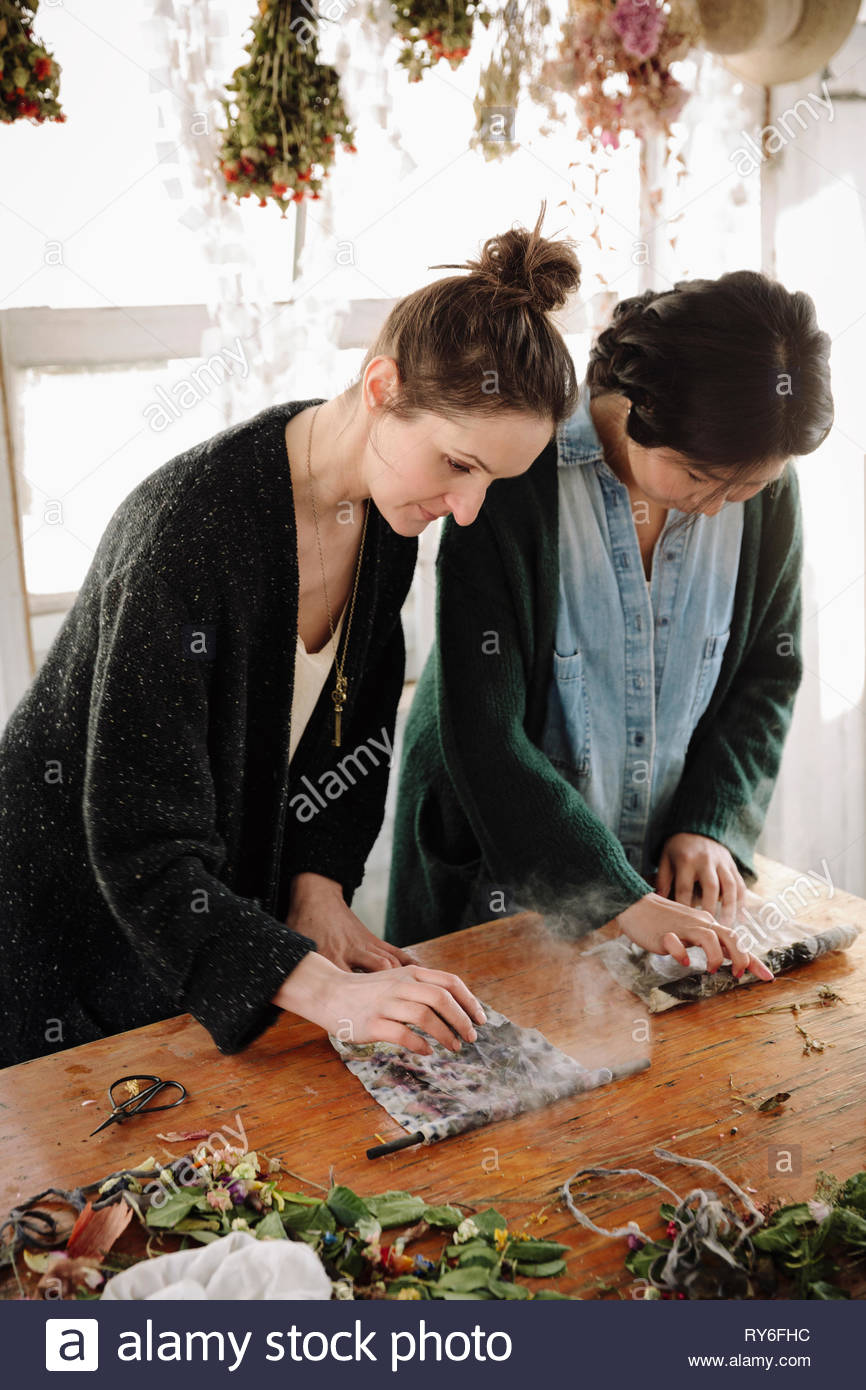 Women drying flowers for paper making - Stock Image