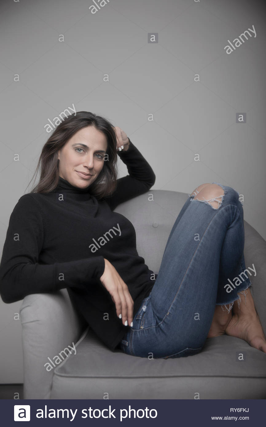 584df126c18 Portrait confident beautiful young woman in sweater and ripped jeans -  Stock Image