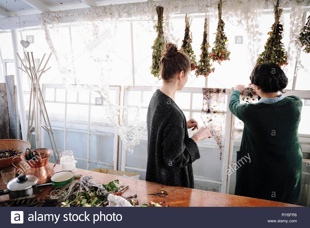 Creative women hanging flowers to dry - Stock Image