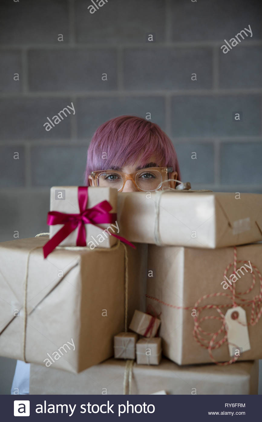 Portrait non-binary gender person carrying stack of christmas gifts - Stock Image