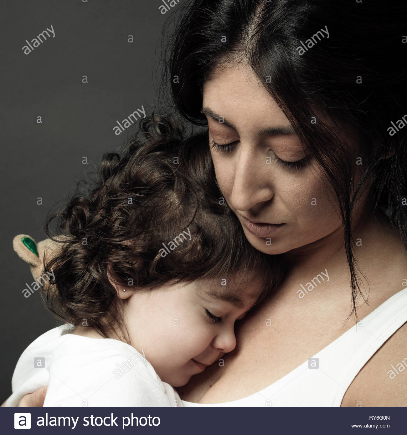 Serene Latina woman holding toddler daughter Stock Photo
