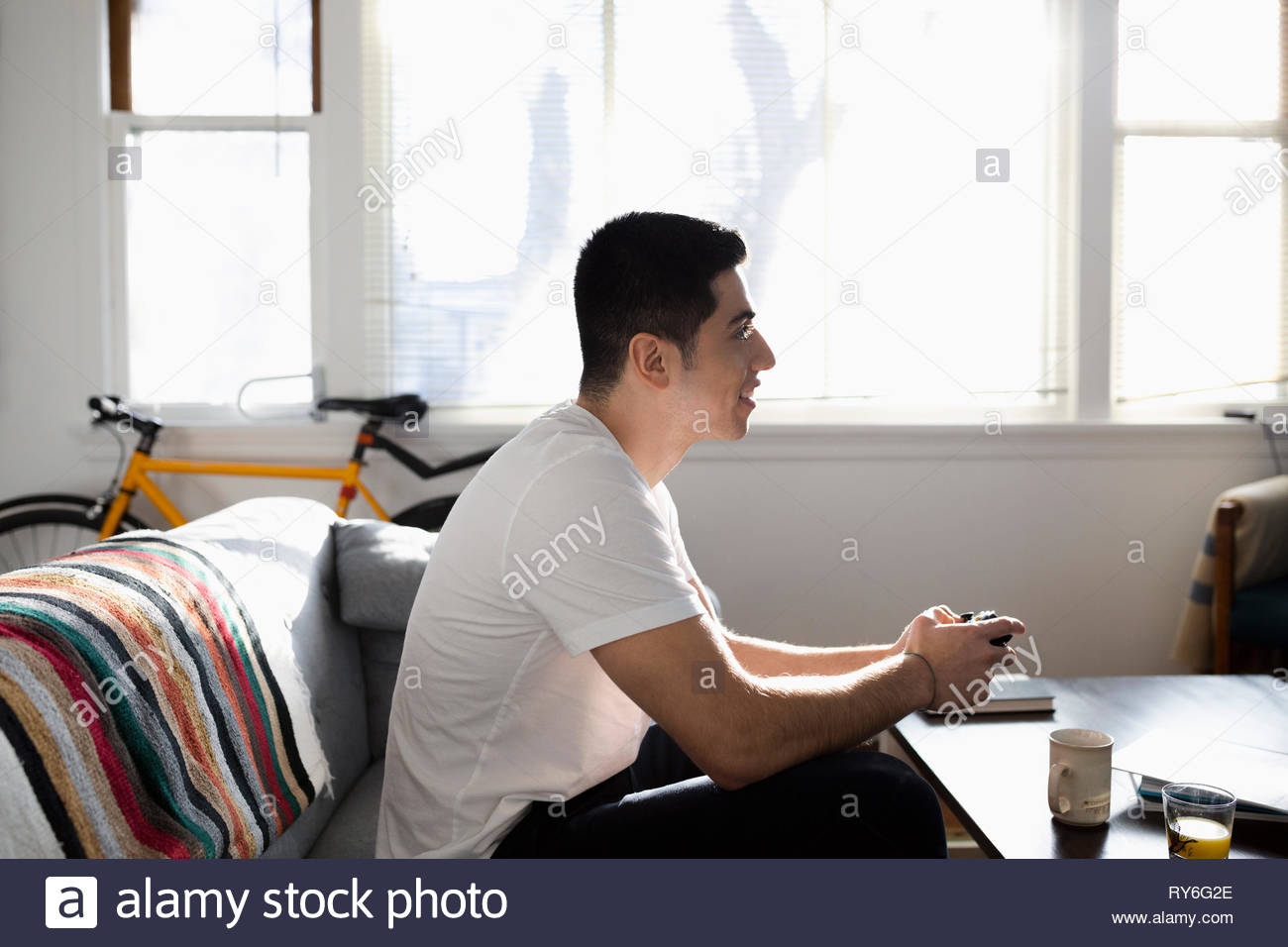 Young Latinx man playing video game in living room - Stock Photo