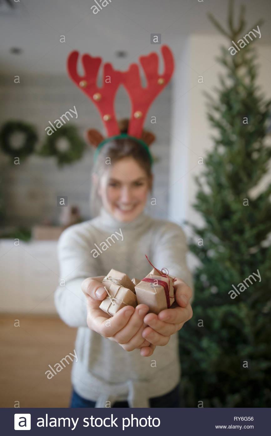 Portrait teenage girl in reindeer antlers holding small christmas gifts - Stock Image