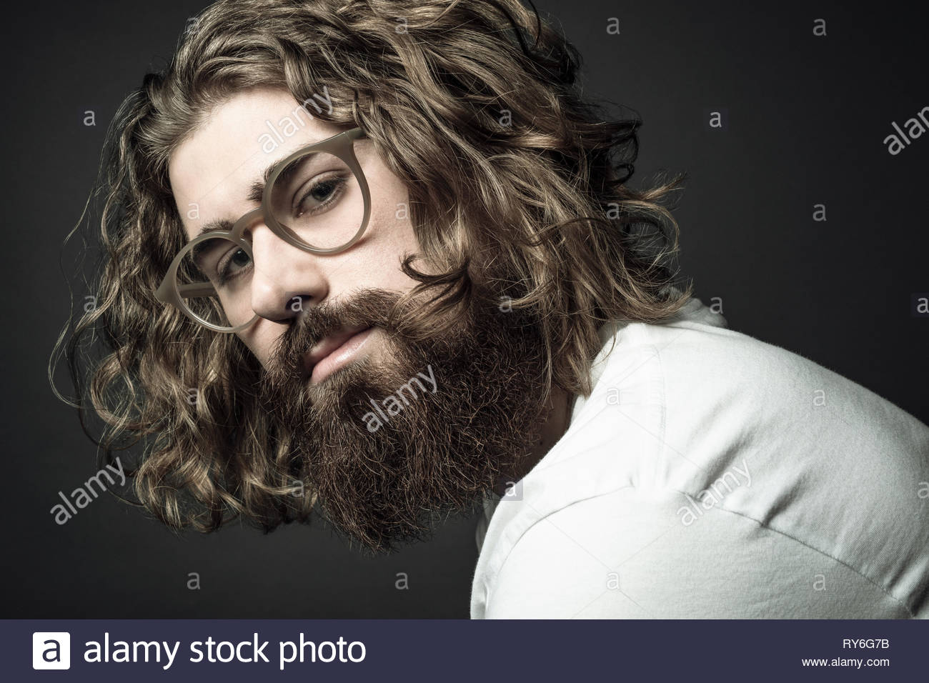 Portrait confident handsome young man with curly long hair and beard - Stock Image