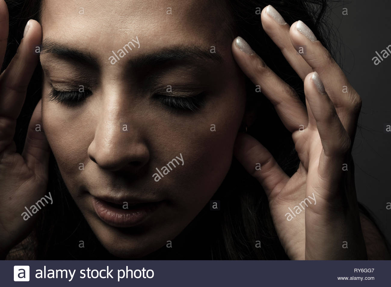Close up portrait beautiful Latina woman with head in hands looking down - Stock Image