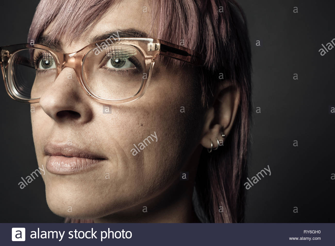 Close up portrait confident beautiful non-binary gender person with pink hair and eyeglasses - Stock Image