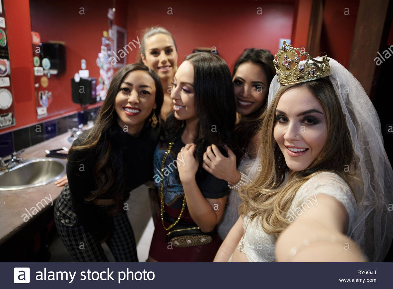 Selfie point of view bachelorette and friends in nightclub bathroom - Stock Image