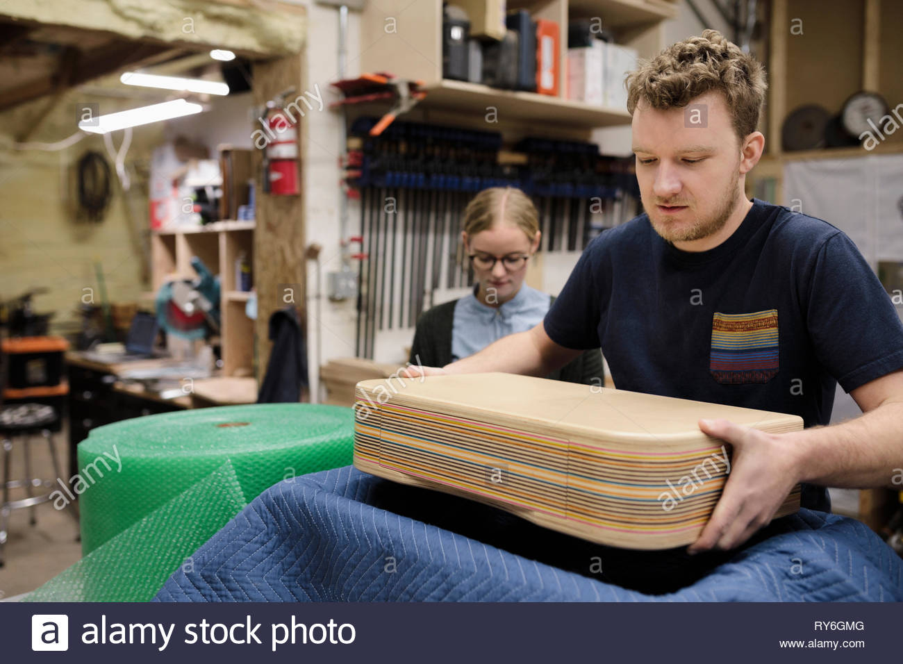 Male artist packaging product in workshop Stock Photo
