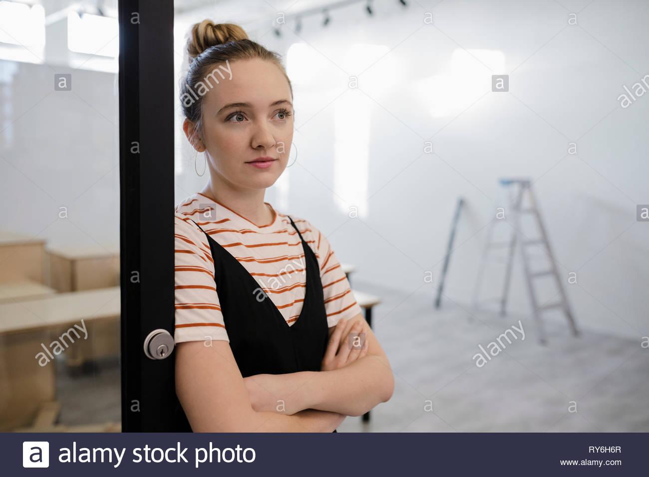 Thoughtful female artist standing in art gallery doorway - Stock Image