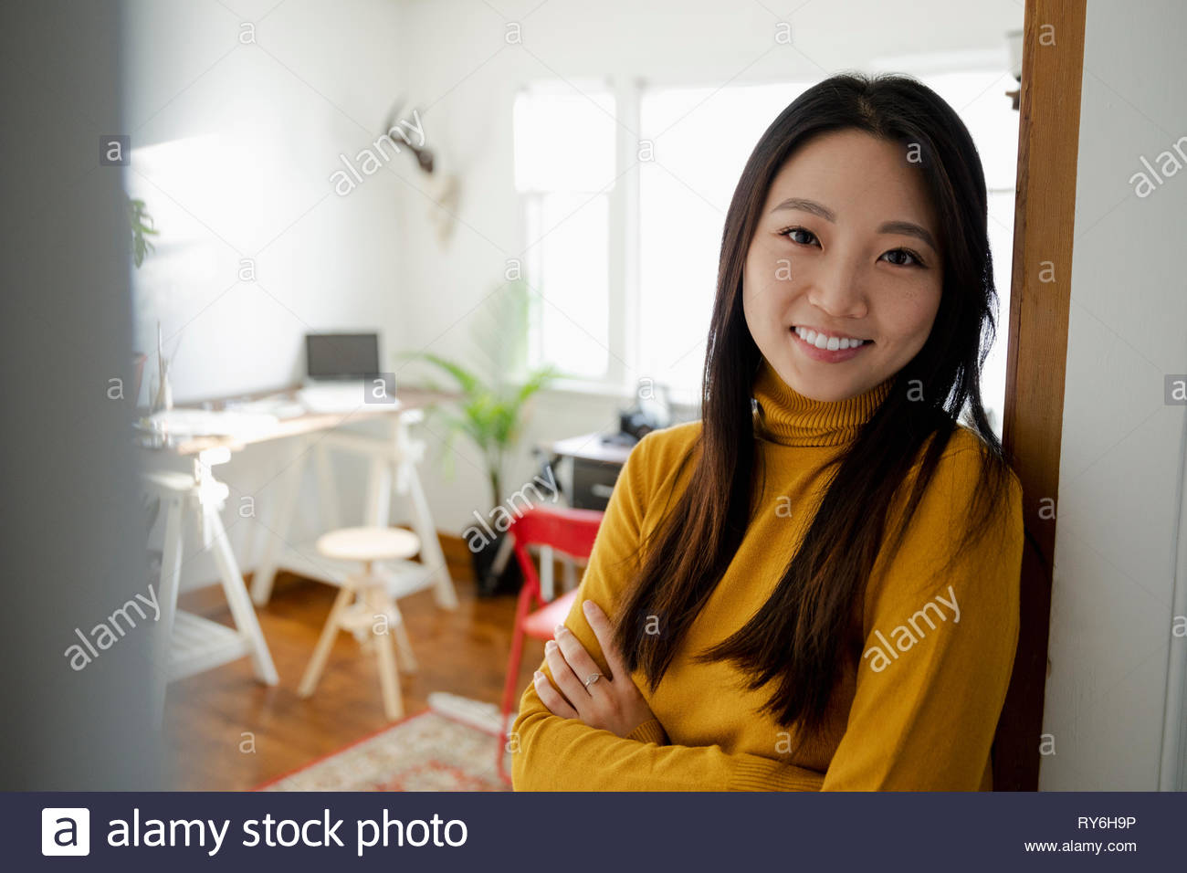 Portrait smiling, confident young woman standing in home office doorway - Stock Image