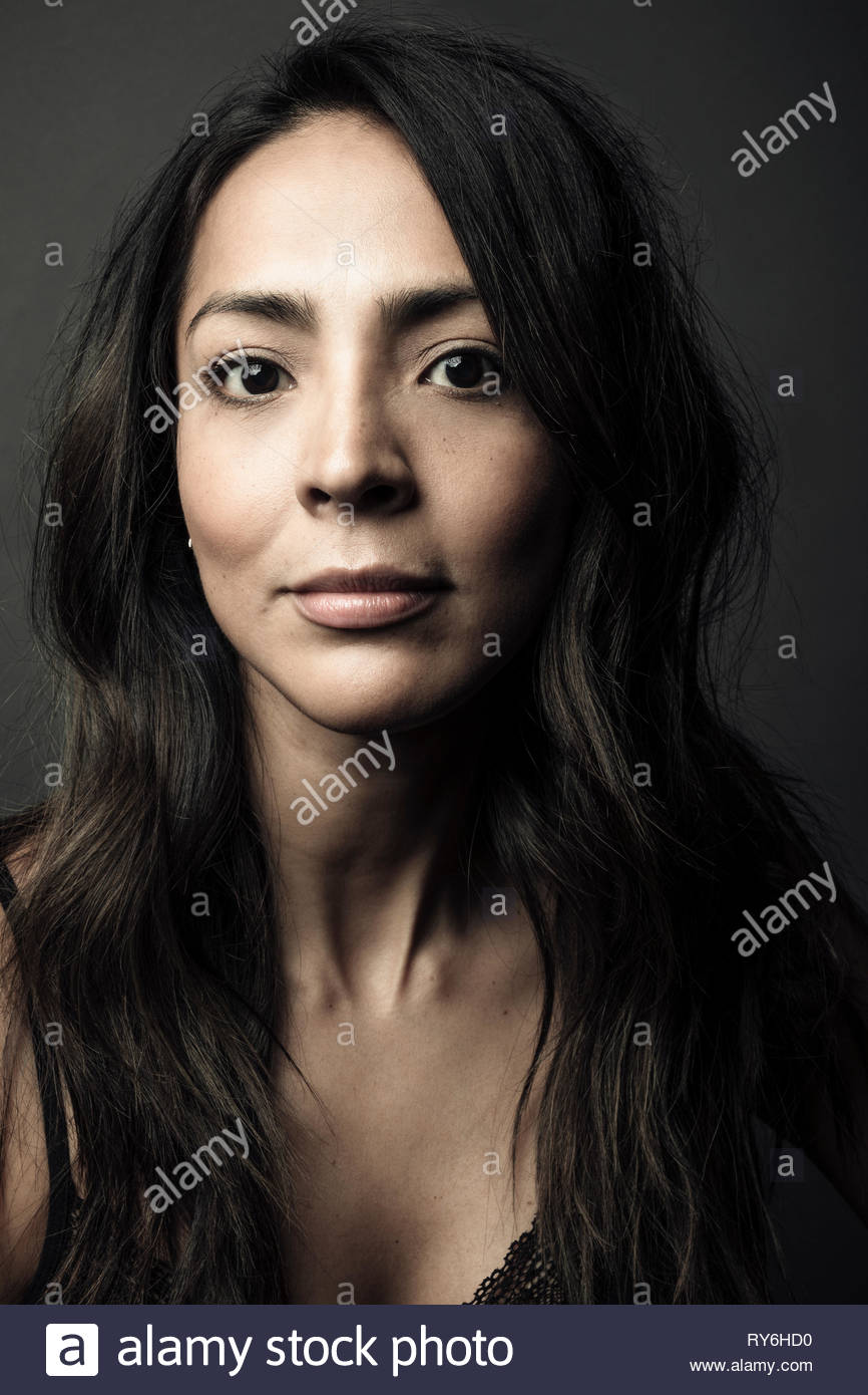 Portrait confident beautiful Latina woman with long black hair and brown eyes - Stock Image