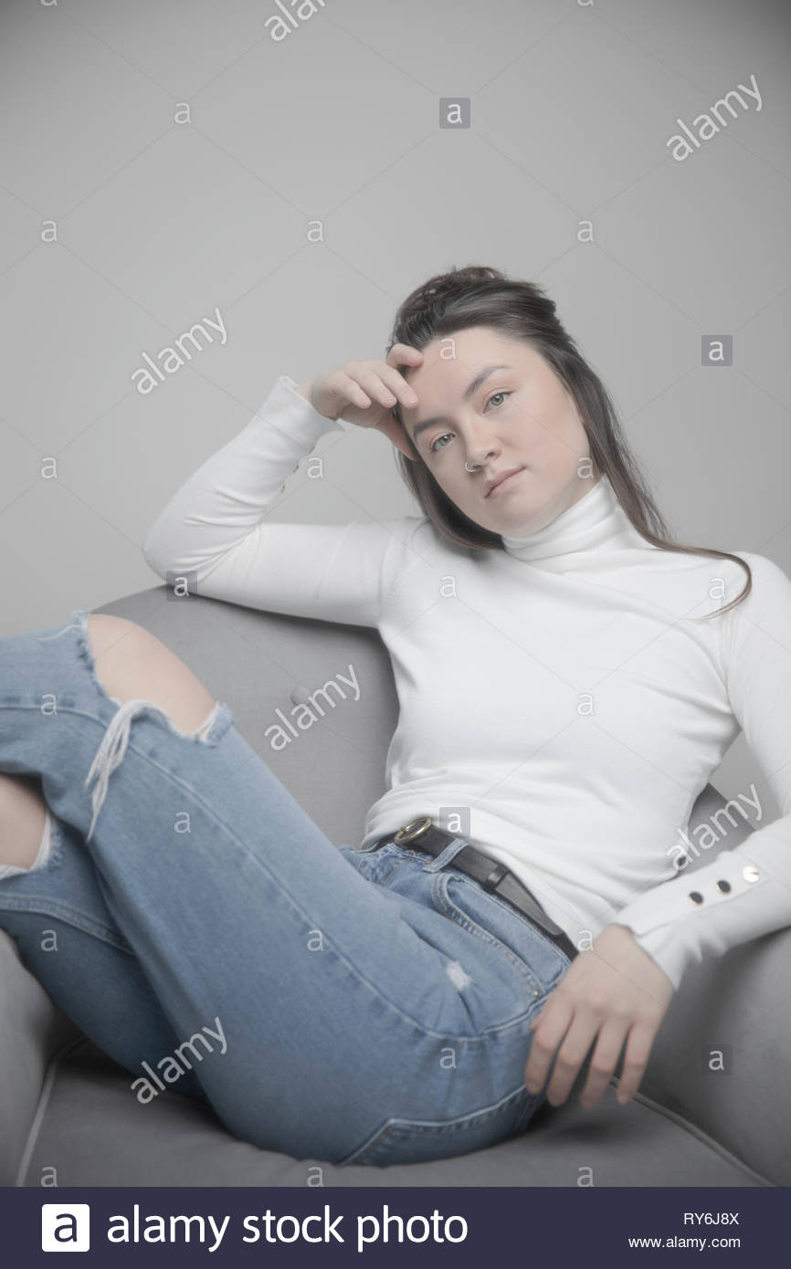 Portrait confident, cool, beautiful young woman in ripped jeans and turtleneck - Stock Image