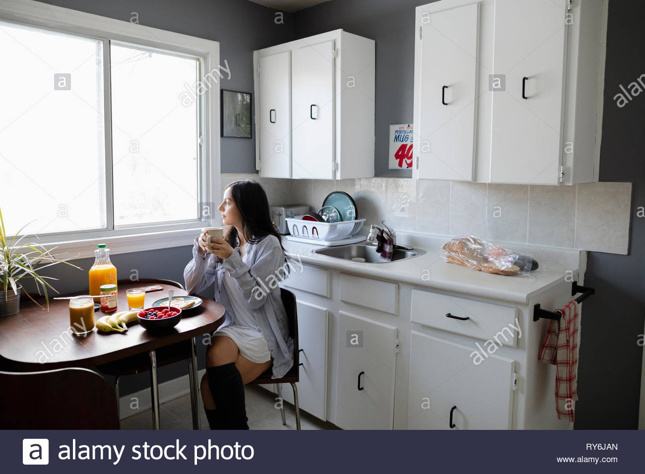 Thoughtful young Latinx woman enjoying breakfast, looking out kitchen window - Stock Image