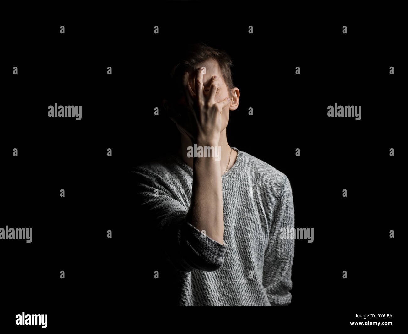 Man covering face with hand while standing against black background - Stock Image