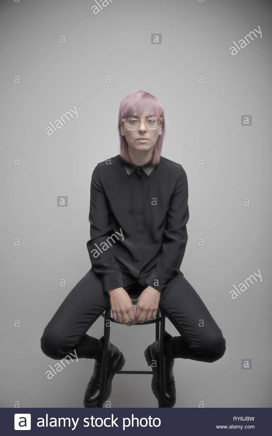 Portrait confident beautiful non-binary gender person with pink hair Stock Photo