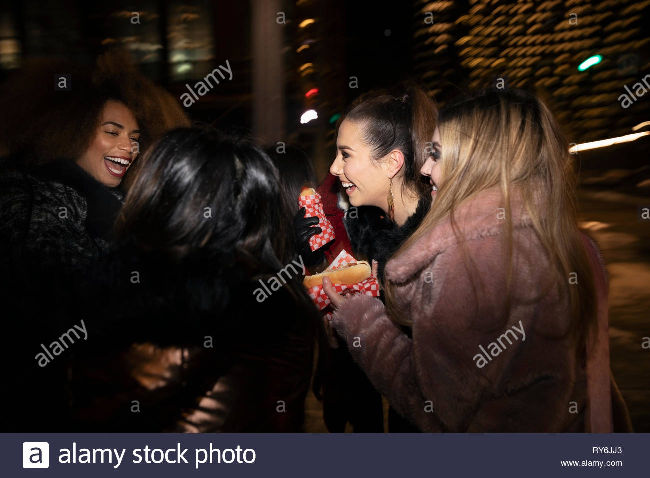 Women friends eating hot dogs on urban street at night - Stock Image