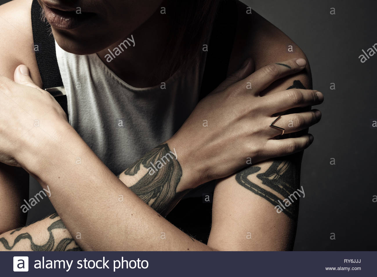 Close up non-binary gender person with tattooed arms - Stock Image
