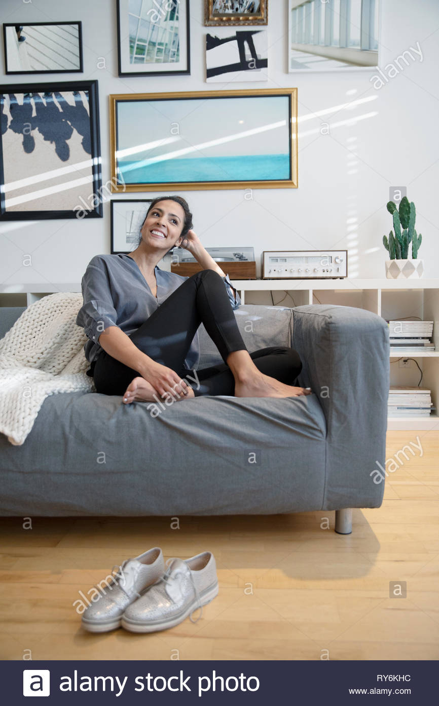 Happy barefoot woman relaxing on living room sofa Stock Photo