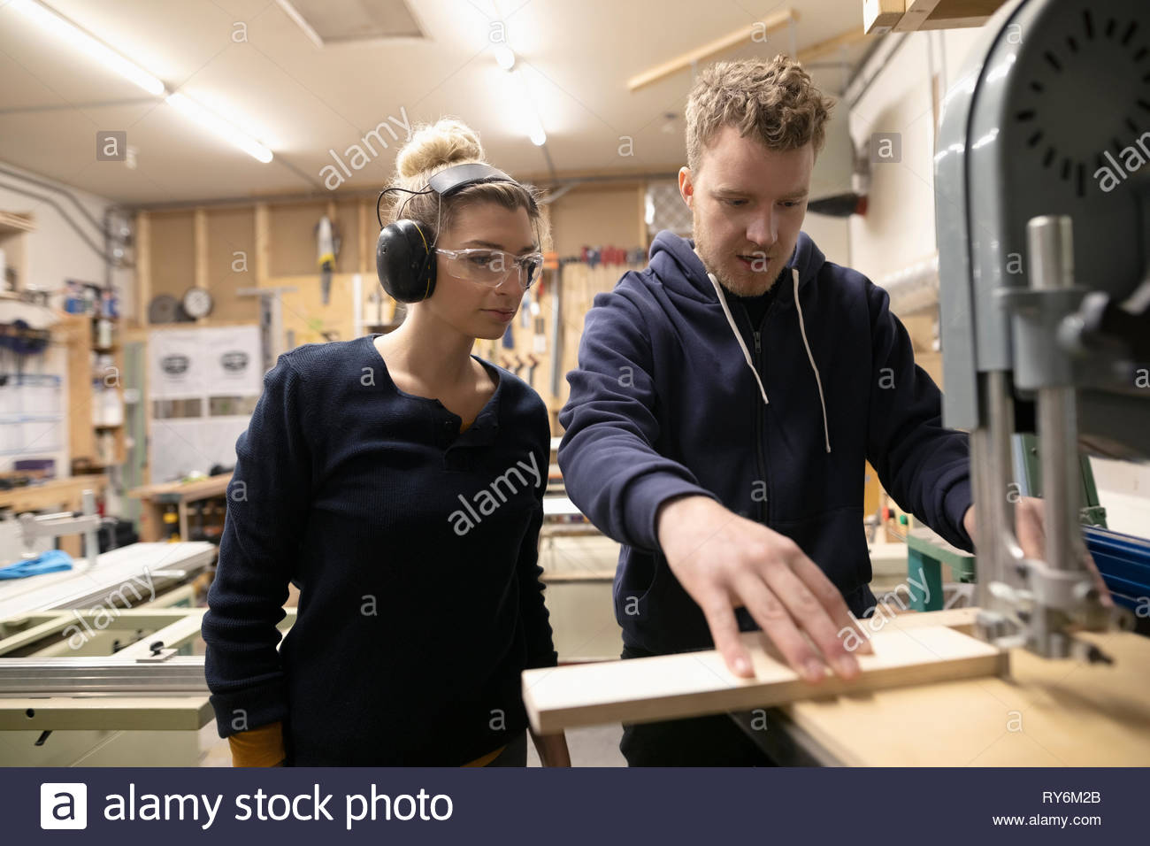 Woodworkers using saw in woodworking shop - Stock Image