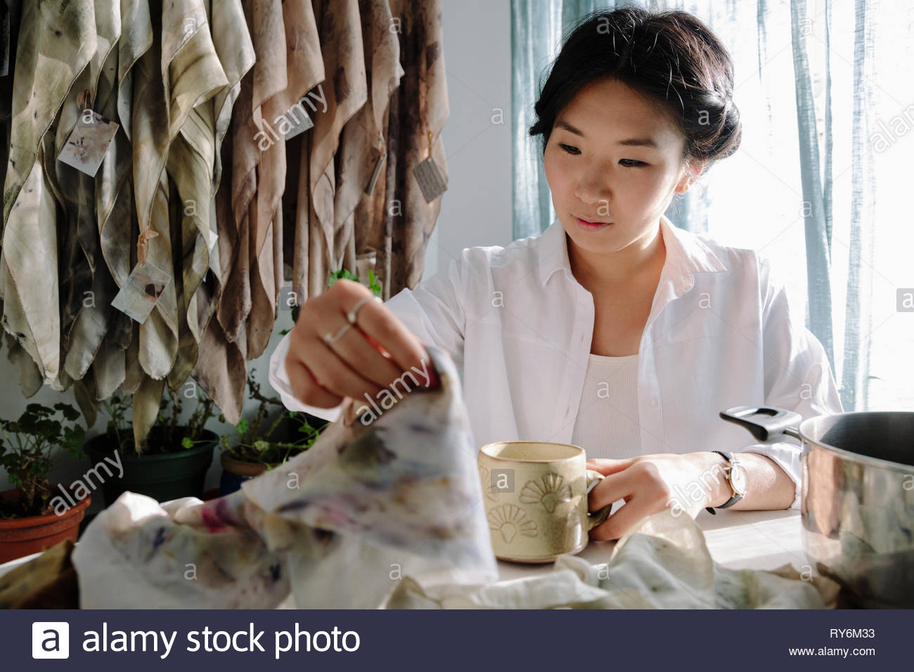 Female artist dyeing clothing with dried flowers at table - Stock Image
