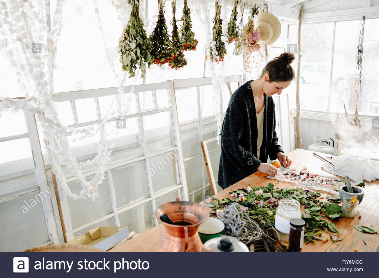 Female artist rolling dried flowers for paper making - Stock Image
