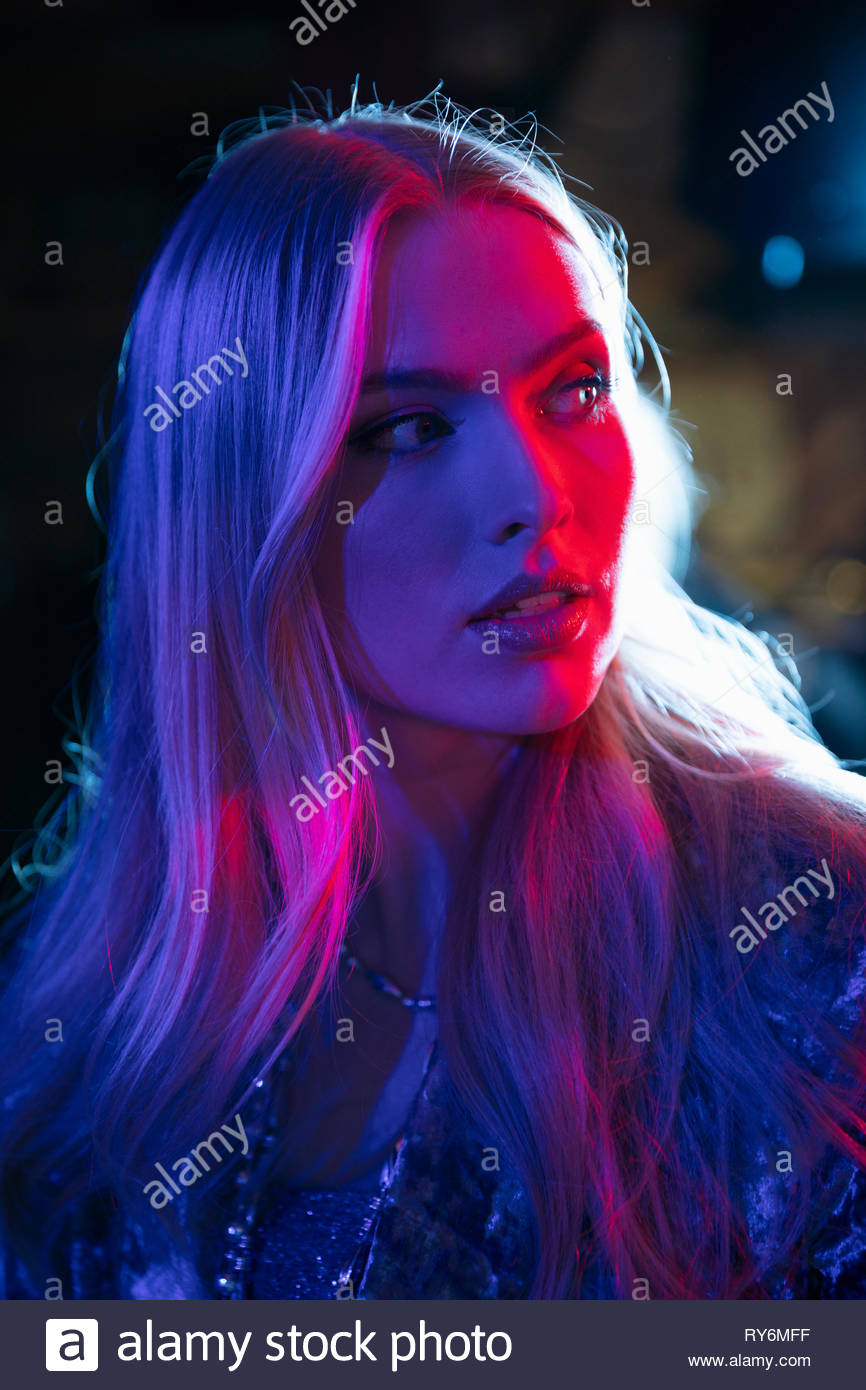 Portrait young woman in dark nightclub - Stock Image