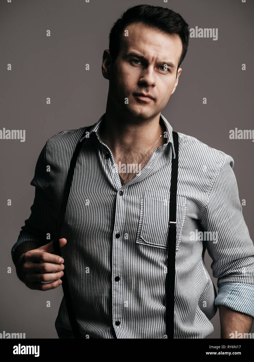 Portrait of handsome businessman wearing suspenders while standing against gray background - Stock Image
