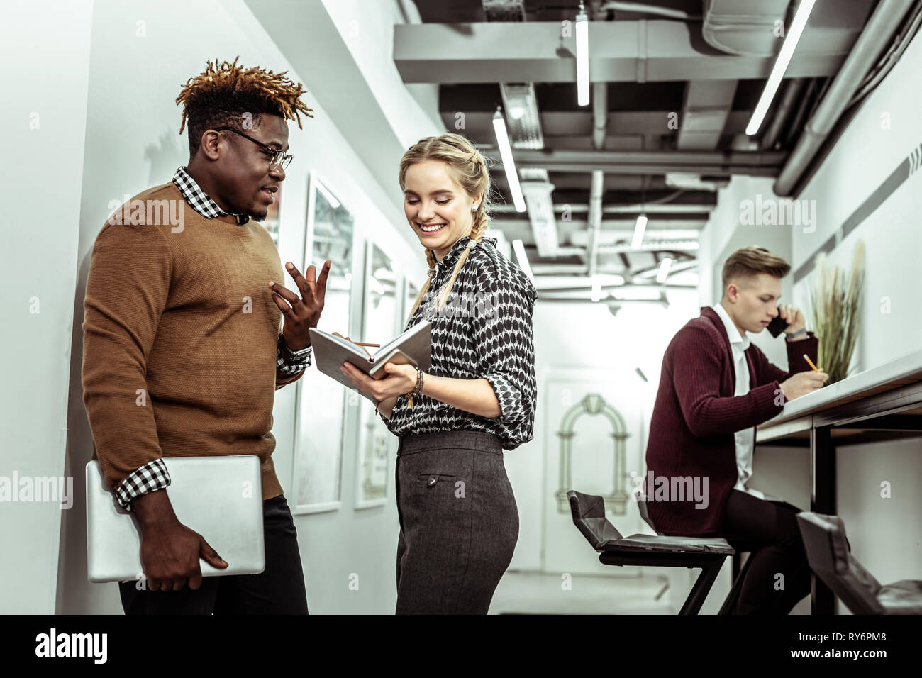 Cheerful young lady with wide smile standing with her colleague - Stock Image