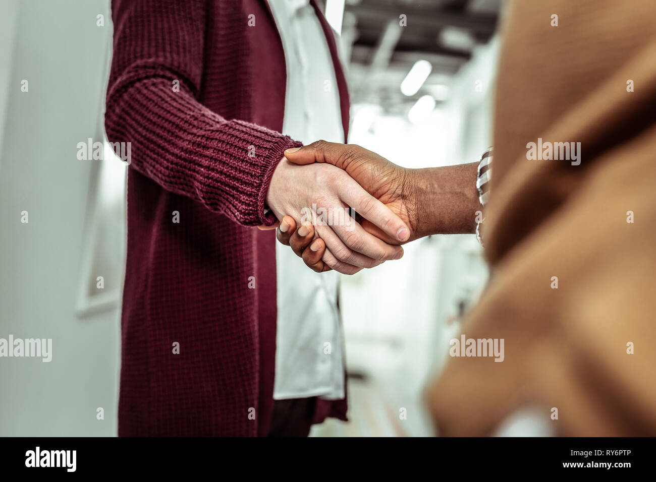 African American dark-skinned man touching hands of his light-skinned workmate - Stock Image