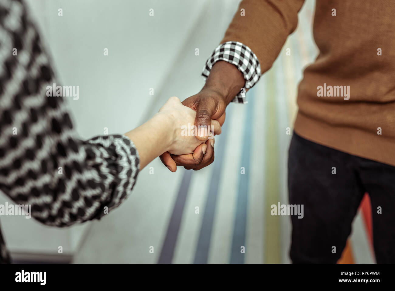 Dark-skinned strong man shaking hands with tiny pale woman - Stock Image