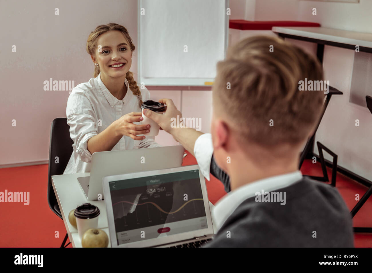 Generous short-haired guy proposing his coffee in cardboard cup to smiling woman - Stock Image