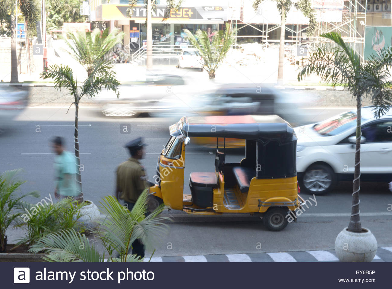 Rickshaw parked on busy street in city - Stock Image