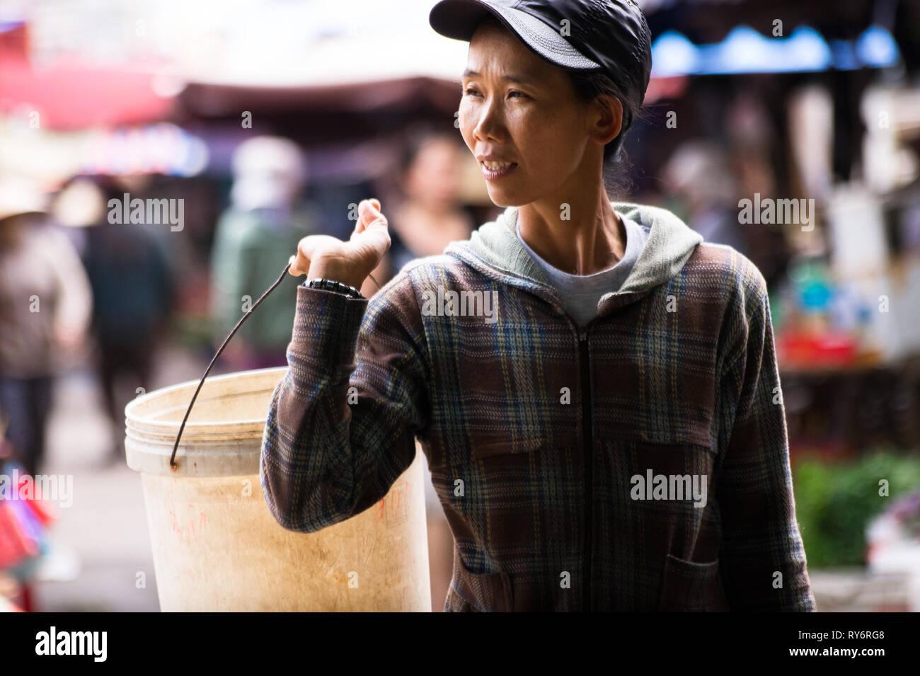 Vietnamese Woman Carrying a Bucket in Hoi An Market, Vietnam - Stock Image