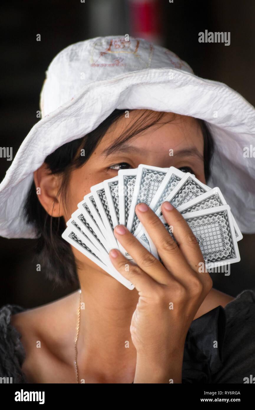 Vietnamese Woman's Face Hiding Behind Playing Cards - Hoi An, Vietnam - Stock Image