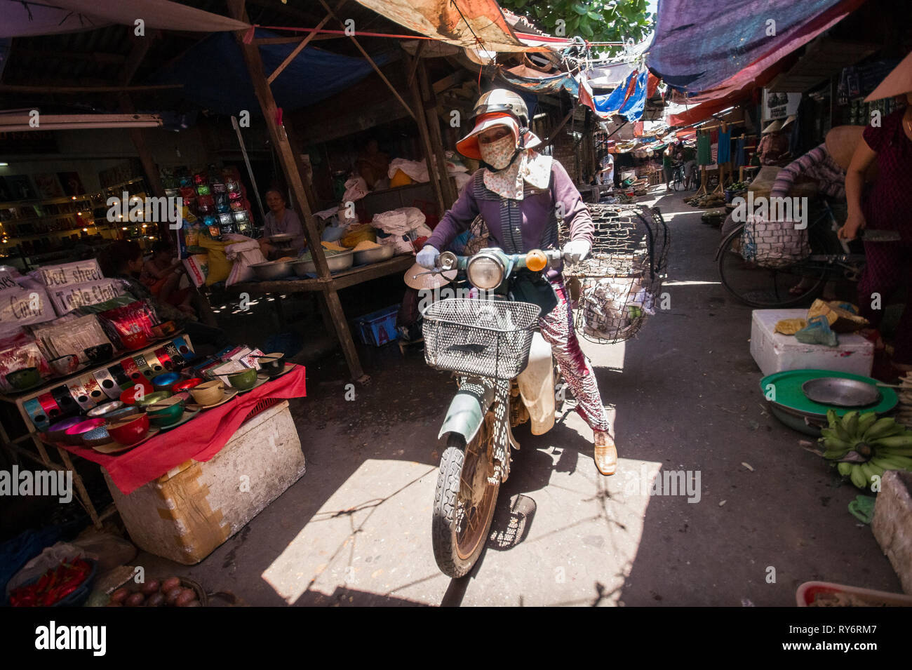 Vietnamese Delivery Woman on Motorbike in Crowded Hoi An Market, Vietnam - Stock Image
