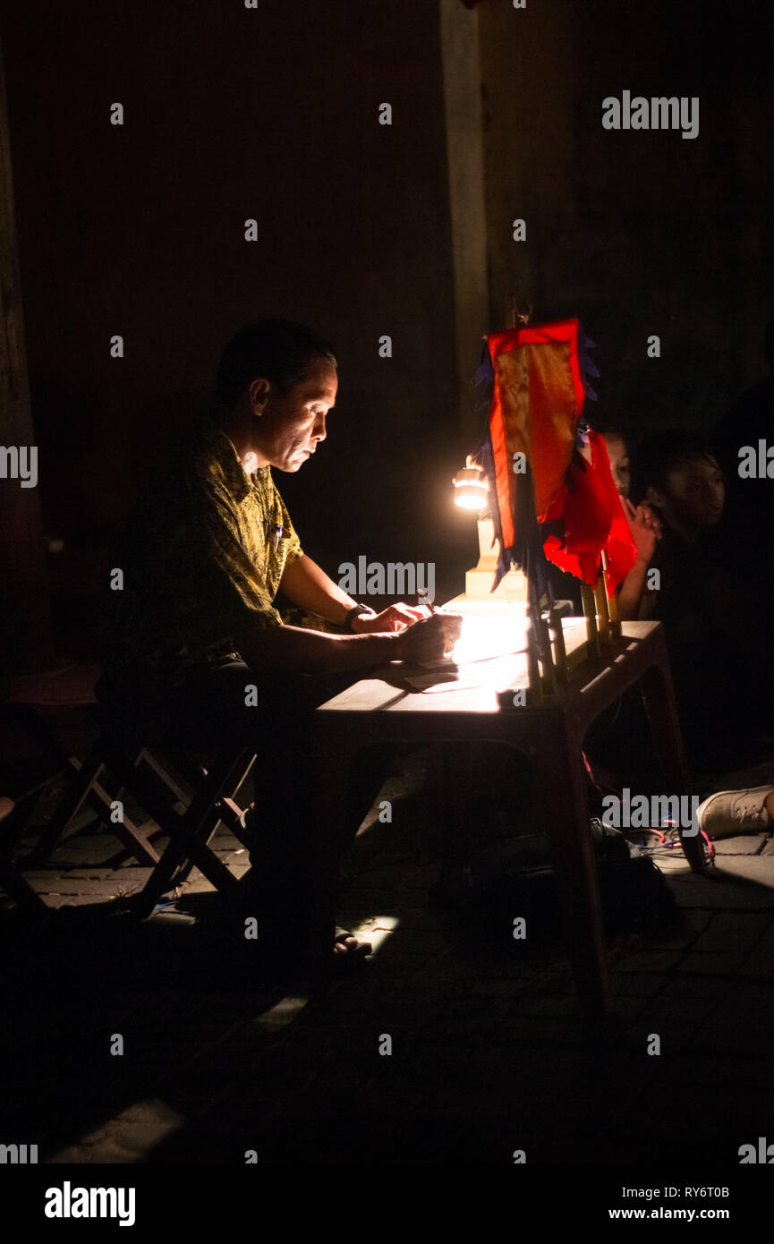 Asian Man Hand Writing By Candlelight on Small Table - Hoi An, Vietnam - Stock Image