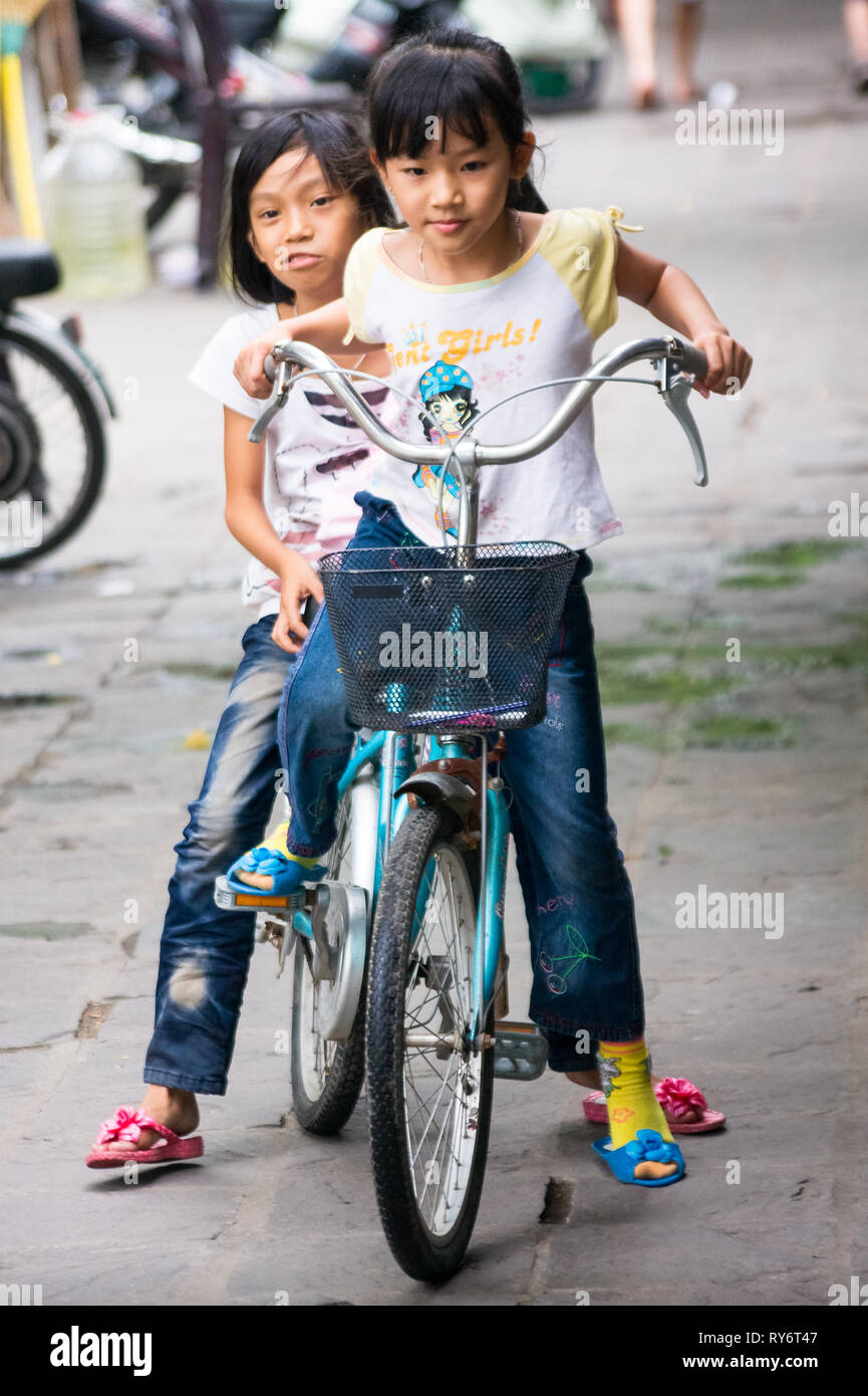 Young Vietnamese Girls Riding Large Bicycle Together on Streets of Hanoi, Vietnam Stock Photo
